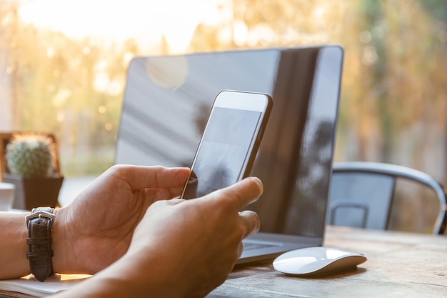 Businessman hands using cell phone with laptop on table in sunlight. Premium Photo