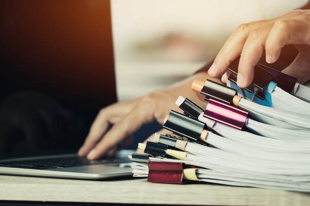 Businessman hands working in stacks of paper files searching information Premium Photo
