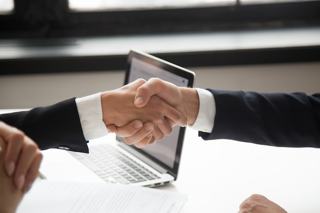Businessman handshaking businesswoman showing respect, closeup view of hands shaking Free Photo