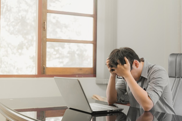 Businessman having stress with laptop computer working in the office Premium Photo