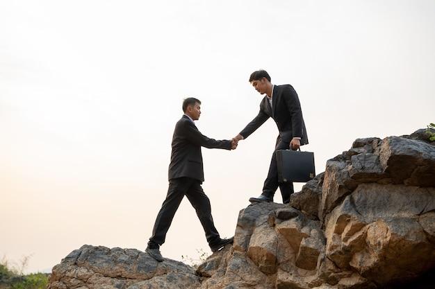 일몰 배경, 비즈니스 팀워크 성공 개념에서 산을 하이킹 서로 돕는 사업가. 프리미엄 사진