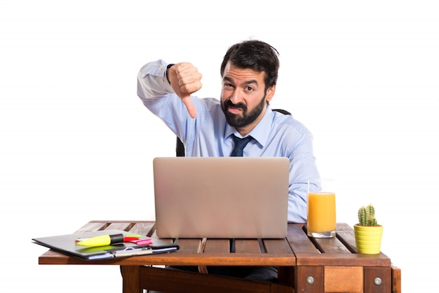 Businessman in his office  doing a bad signal Free Photo