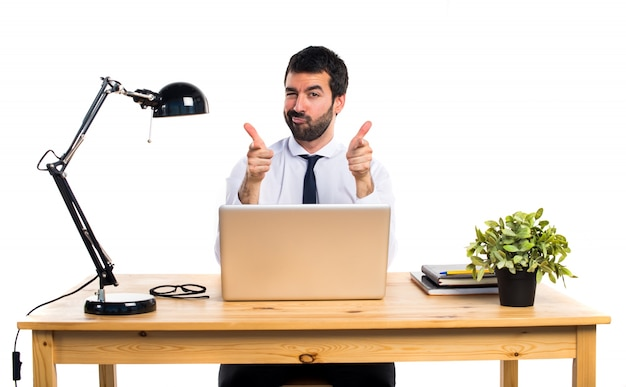Businessman in his office pointing to the front Free Photo
