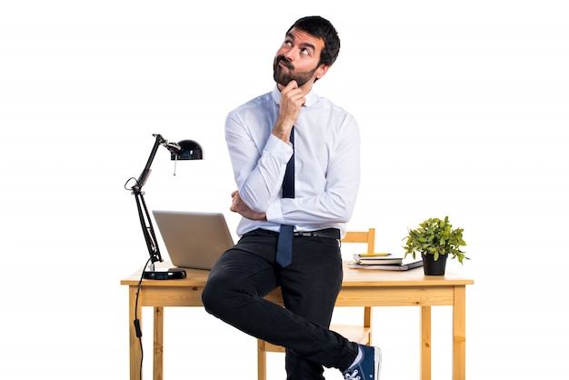 Businessman in his office thinking Free Photo