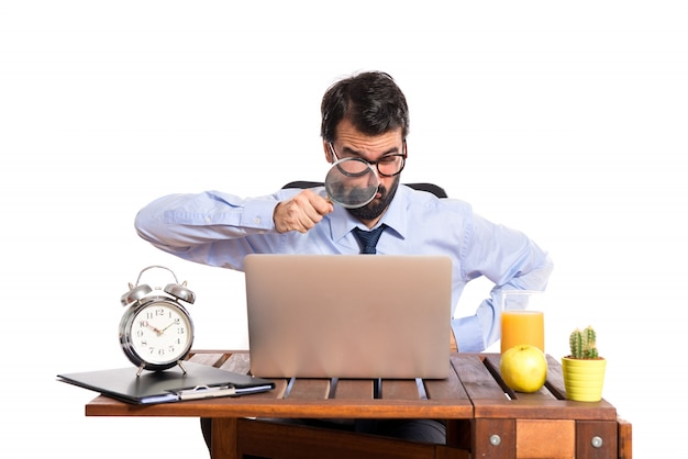 Businessman in his office with magnifying glass Free Photo