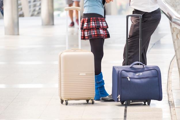 Businessman hold luggage travel passenger bag of tourist traveller on walk way in gate terminal. Premium Photo
