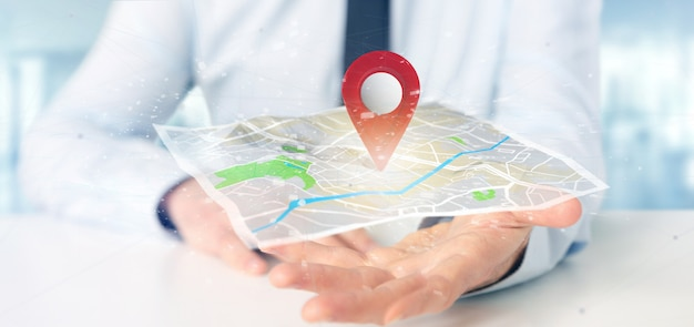 Businessman holding a 3d rendering pin holder on a map Premium Photo