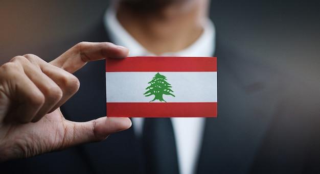 Businessman holding card of lebanon flag Premium Photo