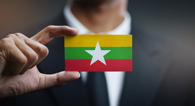 Businessman holding card of myanmar flag Premium Photo