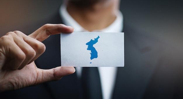 Businessman holding card of unification flag of korea flag Premium Photo