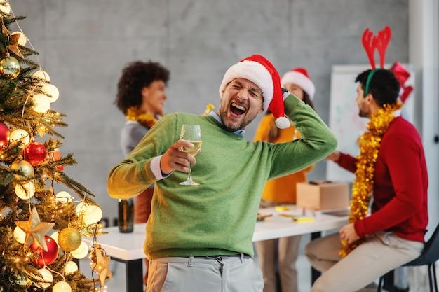 Бизнесмен, держащий шампанское, стоя рядом с елкой в своей фирме в канун рождества. Premium Фотографии