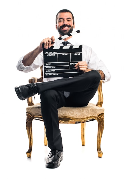 Businessman holding a clapperboard Free Photo
