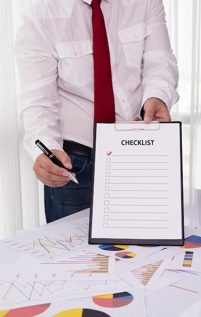 Businessman holding clipboard with checklist against Premium Photo