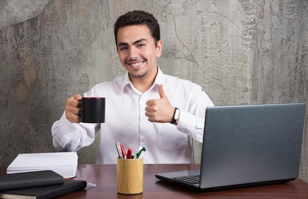 Бизнесмен, держа чашку чая и показывает палец вверх за офисным столом. Бесплатные Фотографии