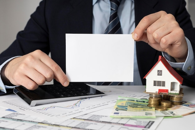 Businessman holding an empty card next to a miniature house Free Photo