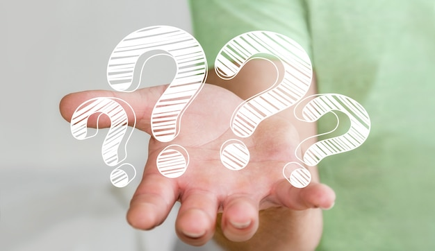 Businessman holding hand drawn question marks in his hand Premium Photo