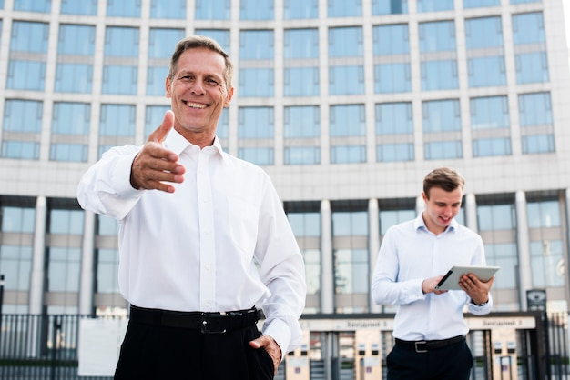 Businessman holding hand out Free Photo