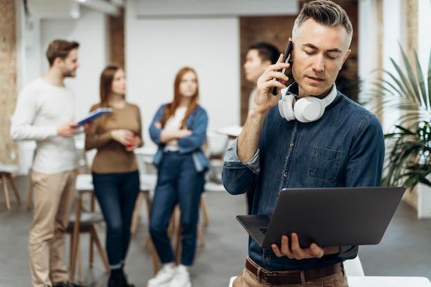 Бизнесмен, держащий свой ноутбук во время разговора по телефону Бесплатные Фотографии