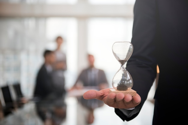 Businessman holding an hour glass, signifies the importance of being on time Free Photo