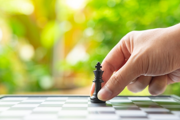 Businessman holding a king chess is placed on a chessboard. Premium Photo