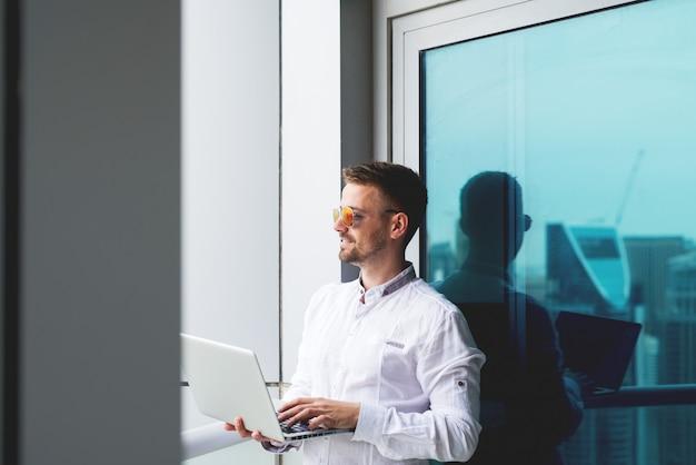 ラップトップオフィスのバルコニーの作業を保持している実業家。 Premium写真