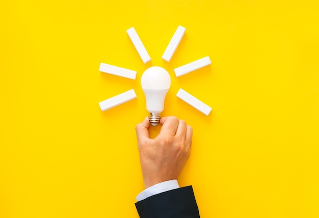 Businessman holding light bulb with wooden blocks with copy space. business start-up goals Premium Photo