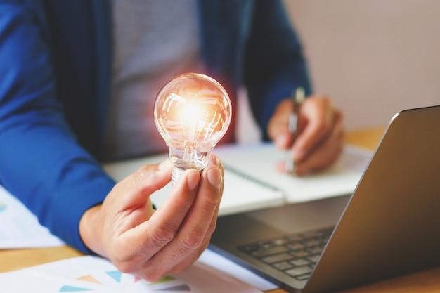 Businessman holding lightbulb in office Premium Photo