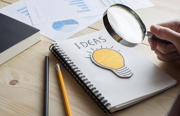 Бизнесмен, держащий лупу с лампочкой. концепция идей творчества бизнеса. Premium Фотографии