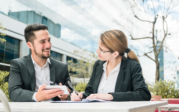 Businessman holding mobile in hand looking at her colleague writing on the document Free Photo