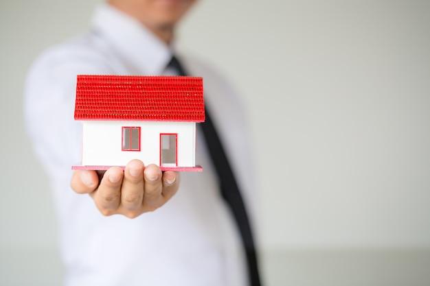 Businessman holding model house Free Photo