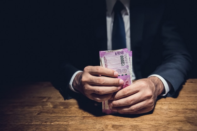 Businessman holding money, indian rupee currency, at the table in dark room Premium Photo