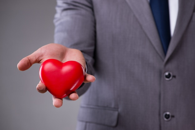 Businessman holding red heart in love concept Premium Photo