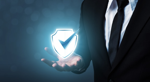 Businessman holding shield protect icon Premium Photo