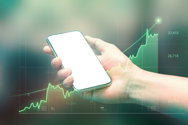 Businessman holding smartphone and showing holographic graphs and stock market statistics gain profits. Premium Photo