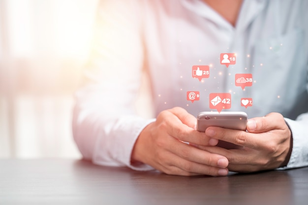Businessman holding smartphone to use social media icon such as love like and star. marketing and business concept. Premium Photo