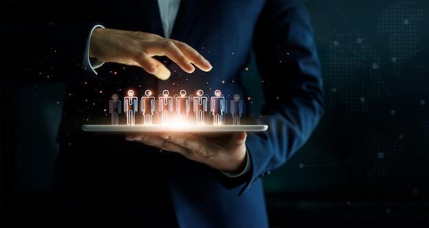 Бизнесмен держа таблетку и группу людей управления в его руке. Premium Фотографии