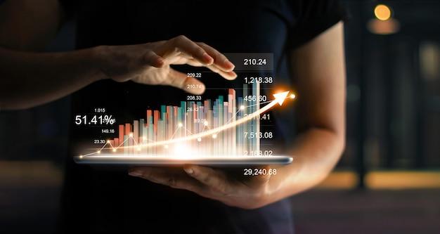사업가 태블릿을 들고 화살표와 통계, 그래프 및 차트의 성장 가상 홀로그램을 보여주는 프리미엄 사진