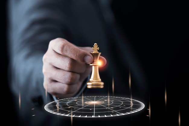 Businessman holding and throwing golden king chess to virtual target dart board. Premium Photo