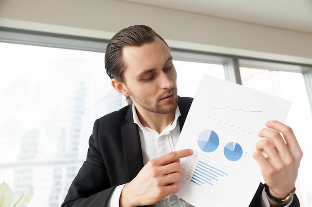 Businessman holds document with infographics Free Photo
