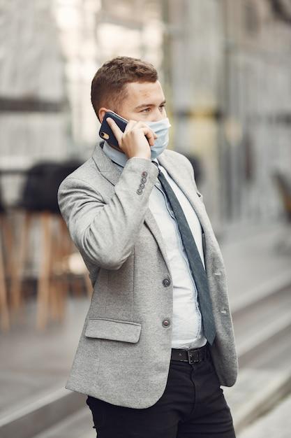 Бизнесмен в городе. человек в маске. парень с телефоном. Бесплатные Фотографии