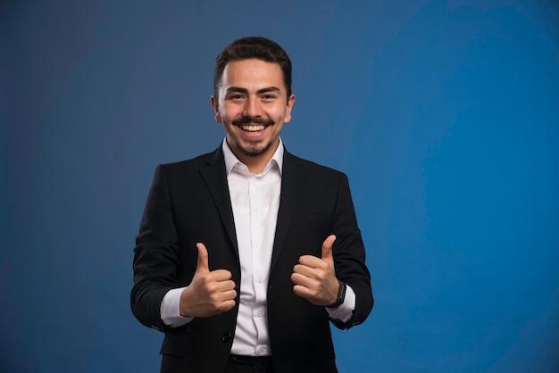 Бизнесмен в черном костюме делает большой палец вверх знак. Бесплатные Фотографии