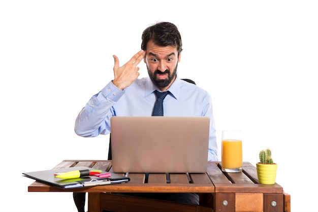 Businessman in his office making suicide gesture Free Photo