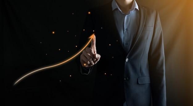 Бизнесмен в костюме рисует пальцем стрелку вверх на черном Premium Фотографии