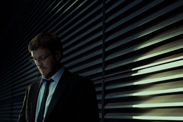 Бизнесмен в костюме, стоя у окна Бесплатные Фотографии