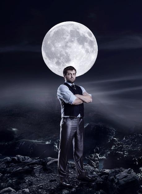 Бизнесмен в ночи против большой луны Premium Фотографии