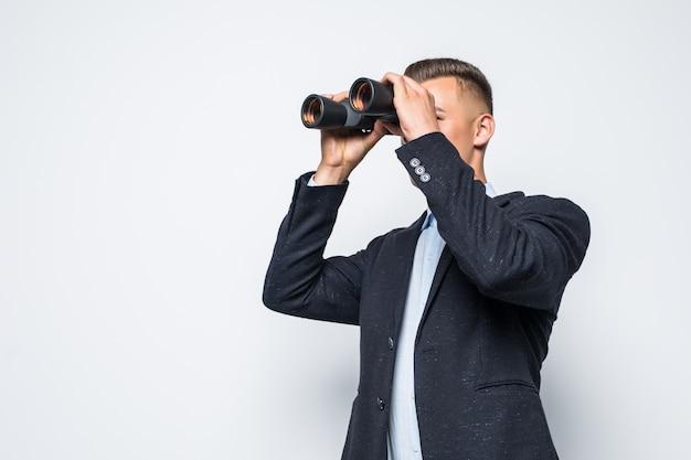 ビジネスマンは白い壁に分離された双眼鏡を通して見ています 無料写真