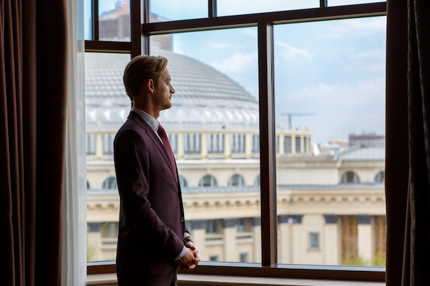 A businessman is standing and looking through the window to the cityscape Premium Photo