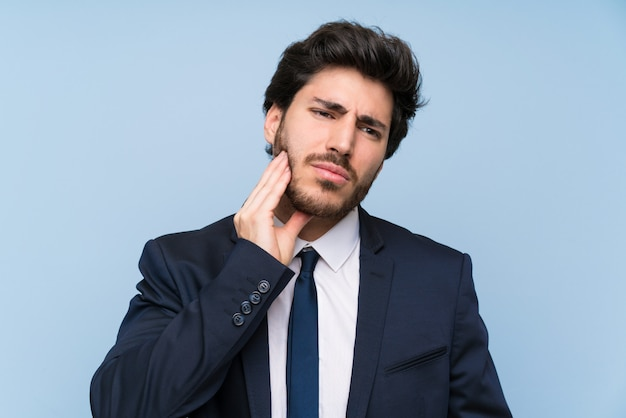 Businessman over isolated blue wall with toothache Premium Photo