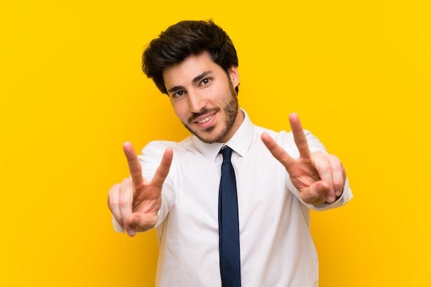 Businessman on isolated yellow  smiling and showing victory sign Premium Photo