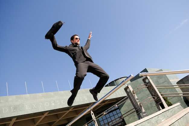 Businessman jumping with a briefcase Free Photo